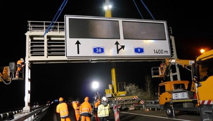 Nächtliche Montage einer Autobahn-Schilderbrücke